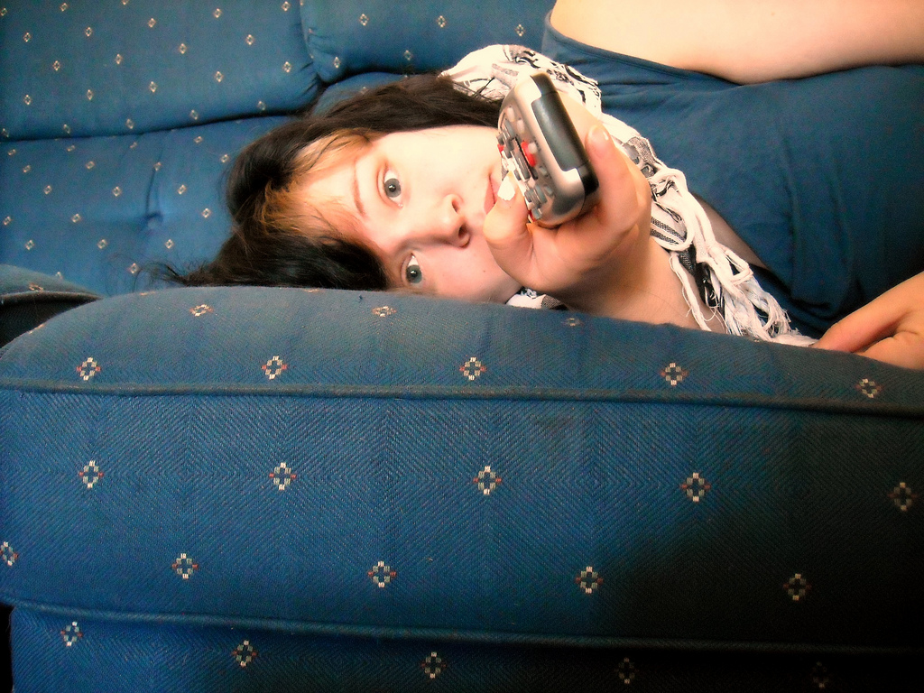 Woman lying on sofa with remote, eyes glazed over.